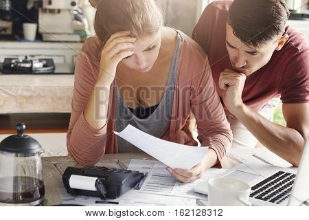 Young Couple Calculating Their Domestic Budget Together In Kitchen, Trying To Save Money For Buying