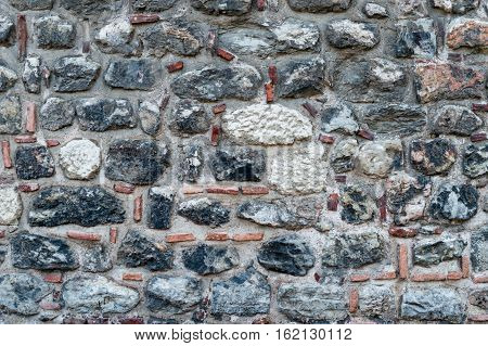 Old stone wall with clay tile and earthenware