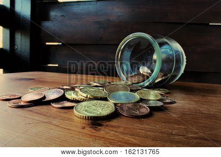 coins falling from the glass bottle on the table