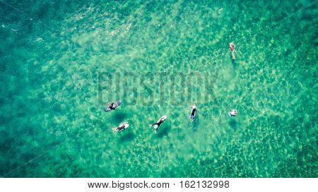 Surfers rest on the surface of the ocean