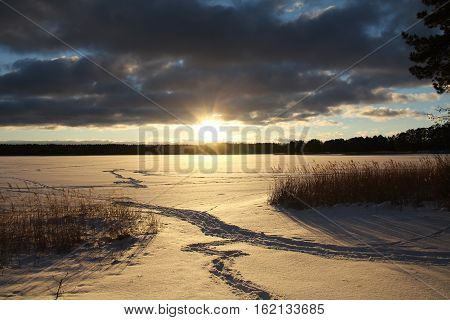 Christmas background with winter forest. Winter landscape with trees beautiful frozen lake and bushes at sunset. Colorful sky.