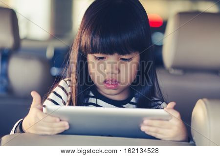 kid play Tablet in car  with vintage color effect