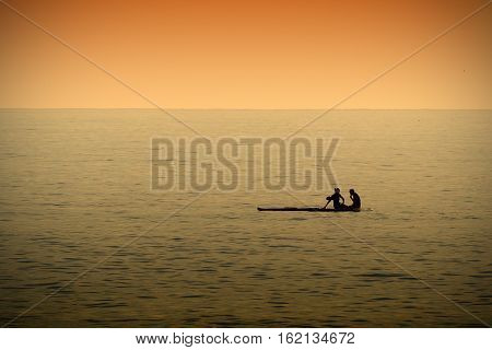 A couple resting while paddleboarding in a calm sea at sunset time. Dark orange atmosphere. Empty copy space for Editor's text.