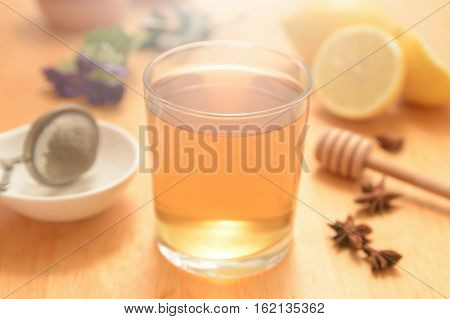 A glass of camomile with some natural honey and anise seeds on a wooden table of a rustic kitchen. Some citrics and herbalist remedies.
