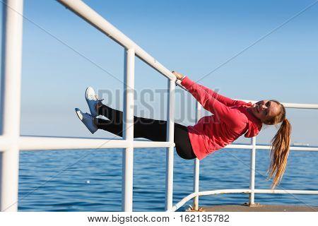 Woman Fool Around Sitting On Handrail Near Sea
