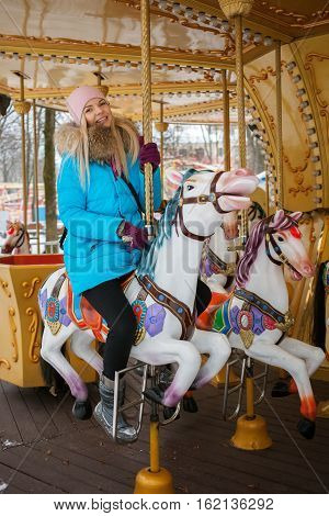 Young Adorable Blonde Woman Enjoys The Winter Holidays On The City Park Carousel. Winter Active City