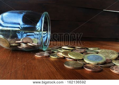 coins faling from glass bottle on the wood table