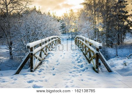 Snowy wooden bridge in a winter day. Stare Juchy Poland