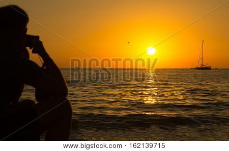 stunning views of the sea orange sunset with a sailboat in the distance