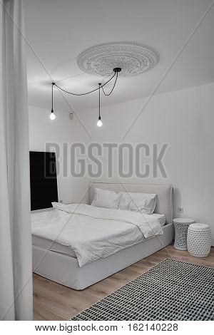 Bedroom in a modern style with white walls and a parquet with a carpet on the floor. There is a bed with white pillows and a blanket, design nightstands, hanging glowing lamps, white bass-relief.