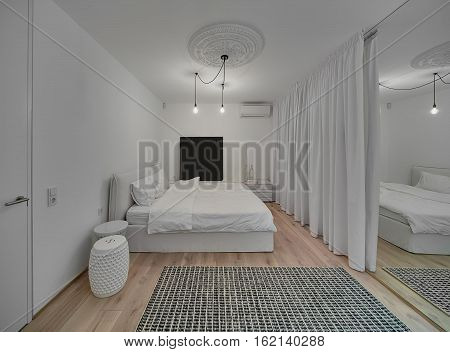 Modern bedroom with white walls and a parquet with a carpet on the floor. There is a bed with white pillows and blanket, design nightstands, hanging glowing lamps, white bass-relief, mirror, curtains.