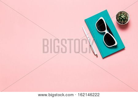 Creative flat lay photo of workspace desk with aquamarine notebook, eyeglasses, cactus with copy space pink background, minimal style.