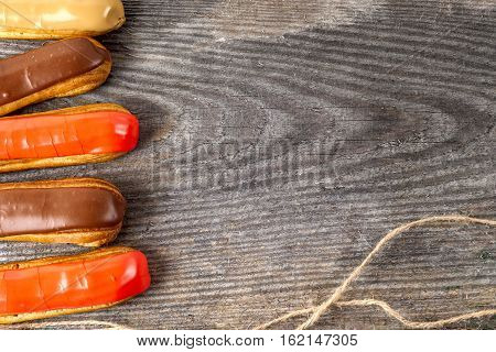 Tasty eclairs on table on rustic wooden background close up. Copy space for text.