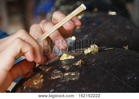 Buddhists make meritGilding gold leaf to round stones embedded call LukNimitr for worship Buddha. Selective focus.