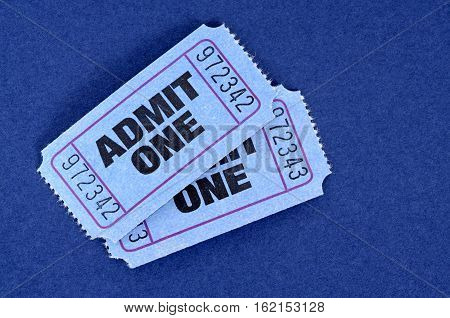 Admit one tickets pair on blue background