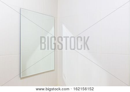 Mirror and white tile wall in bathroom.