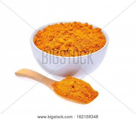 dry turmeric powder in white bowl and wooden spoon isolated on white background