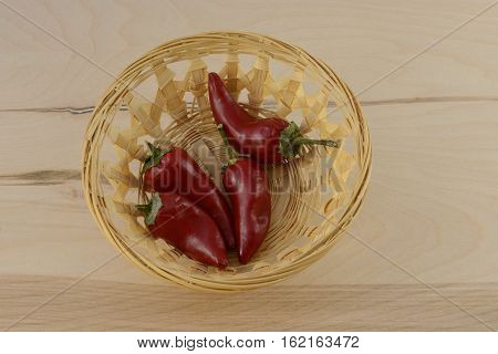 Red chili peppers in wooden wicket basket on wood table