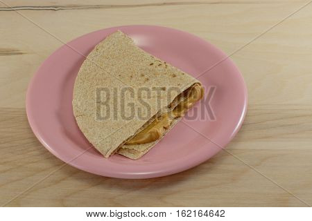 Peanut butter sandwich with whole wheat tortilla bread on pink plate