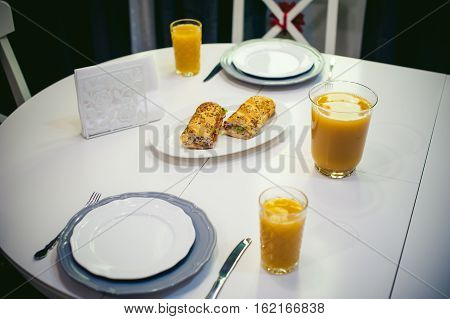 Breakfast Sandwich And Peach Juice. On The Table In The Bright Interior Of The Kitchen In A Plate Is