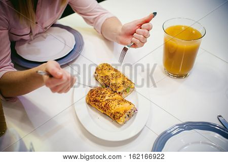 Pretty Blonde Woman In Pink Shirt, Eating At Home Fork And Knife. Breakfast Sandwich And Peach Juice