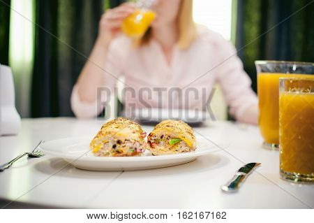 Pretty Blonde Woman In A Pink Shirt, Eating At Home. Breakfast Sandwich And Peach Juice. On White Ta