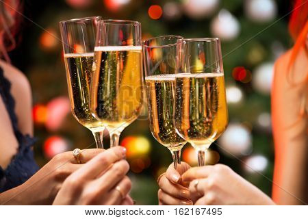 Women's hands with glasses of champagne. X-mas.