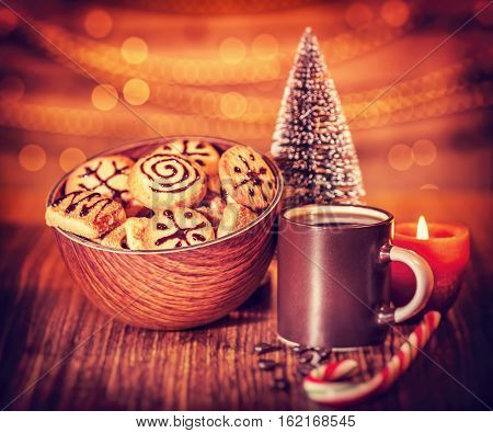 Christmas ginger cookies with coffee cup on the wooden table, candle and candy cane over bokeh festoon background, beautiful festive still life, sweet treats for Santa