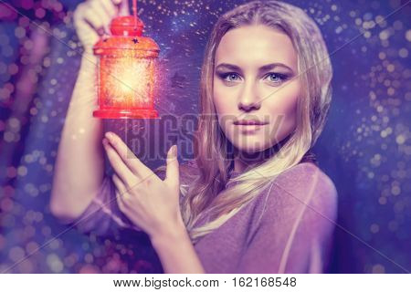 Portrait of a beautiful woman with glowing lantern at nighttime, magical Christmas night, Christmastime fairytale