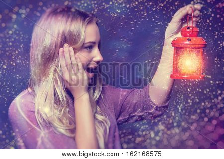 Portrait of a beautiful excited woman surprised looking on a glowing light in lantern, true miracle in Christmas eve, happy magical night