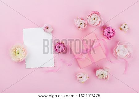 Gift or present box white paper blank and beautiful spring flower on pink desk from above for wedding mockup or greeting card on womans day in flat lay style.