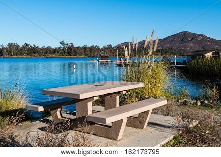 Picnic table at Lake Murray in San Diego, California with boat rental dock and Cowles Mountain in the background,