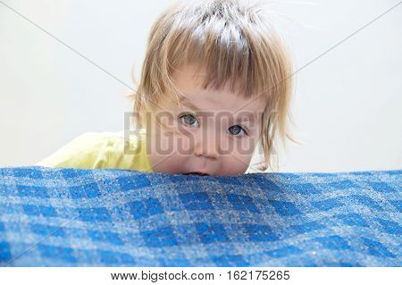 Little girl playing peeking from bed playful child portrait
