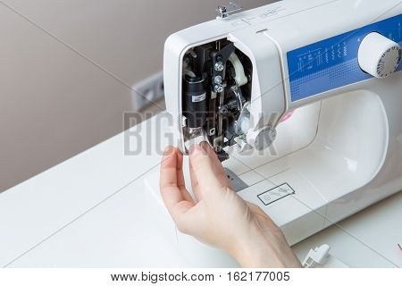 Young man repairing sewing machine