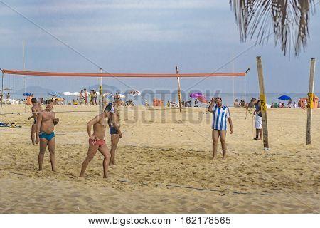 RIO DE JANEIRO, BRAZIL, JANUARY - 2016 - Group of men playing volleyball at copacabana beach in Rio de Janeiro Brazil