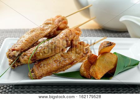 Fried chicken wings with potato on white dish