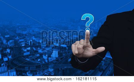 Businessman pressing question mark sign icon over city tower and street blue tone background Customer support concept