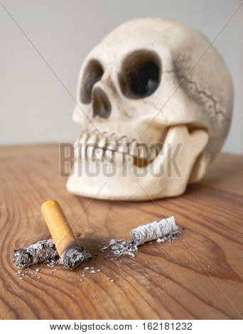 Close up of cigarette stub and blurred human skull