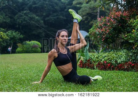 Sporty flexible young woman doing hamstrings stretching exercises on grass outdoors. Active fit girl training in park.