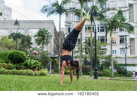 Pretty slim girl standing in downward facing tree pose in city park. Young sporty woman working out doing yoga exercises, handstand.
