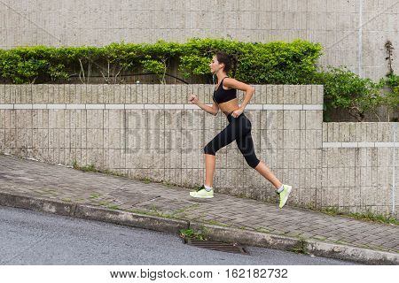 Slim young woman running uphill on sidewalk of city street. Female athlete training outside.