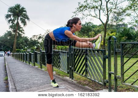 Young athletic woman doing warming-up exercises, stretching her legs on fence at road before running.