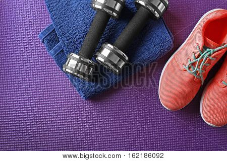 Sport clothes and equipment on color background, top view