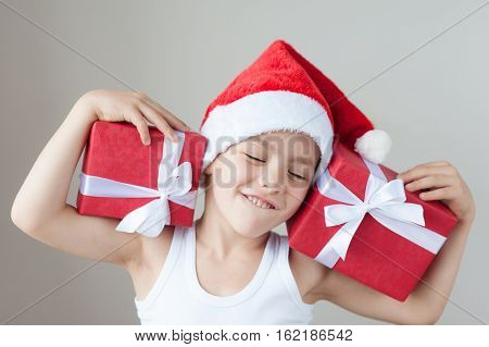 happy boy in santa hat and t-shirt holding two gift boxes on shoulders covering his eyes with pleasure