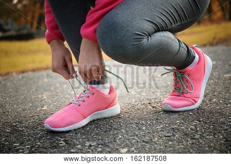 Woman tying up jogging shoes on ground