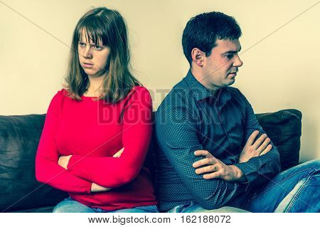 Displeased Couple Sitting Back To Back On Couch
