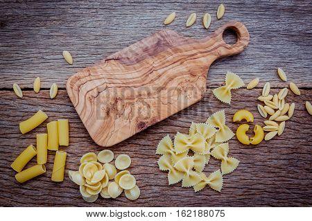 Various Kind Of Pasta Farfalle,fettucini,elbow Macaroni And Rigatoni  Setup On Shabby Wooden Backgro