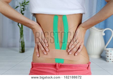 Female back with applied physio tape indoors