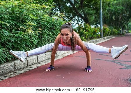 Sporty fit young woman doing handstand exercise in firefly posture. Female athlete working out in the park