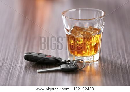 Glass with alcoholic beverage and car key on wooden table. Don't drink and drive concept